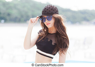A young girl in a black cap, a black bathing suit and blue...