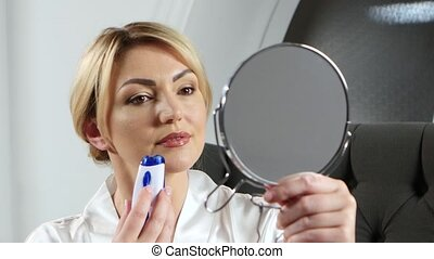 Woman holding a hand holds a mirror and doing epilation on...