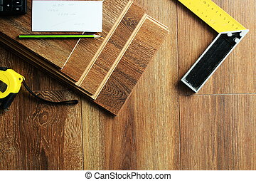 Laminate floor planks and tools on wooden background