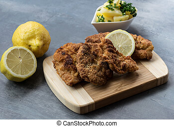 Pork schnitzel with lemon and diced potatoes