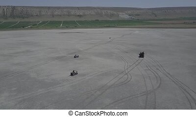 Aerial view of ATV driving down a beautiful wide open beach...