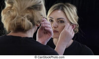 Woman looks in the mirror and adjusts her eyebrows tweezers....