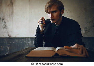 Portrait of handsome young catholic priest praying to God. Dark style, concept doubt