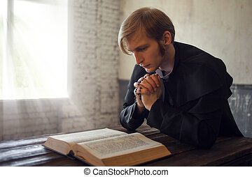 Portrait of handsome young catholic priest praying to God.