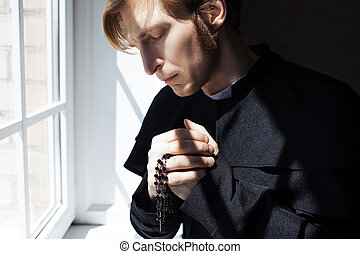 Portrait of handsome young catholic priest praying to God. -...