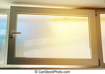 Open PVC basement window with sunlight shining in