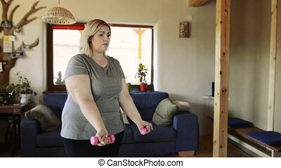 Attractive overweight woman at home working her biceps with...