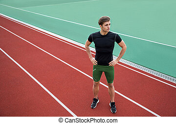Handsome young male athlete standing outdoors