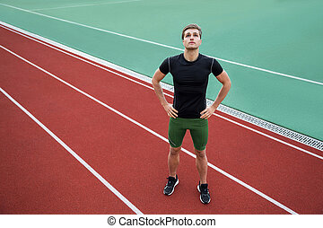 Attractive young male athlete standing outdoors