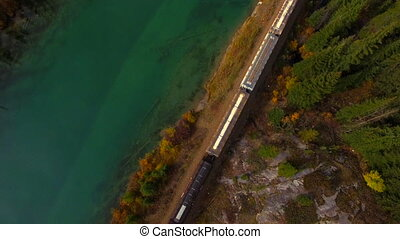Train dashing Rocky Mountains - Banff cargo train aerial...