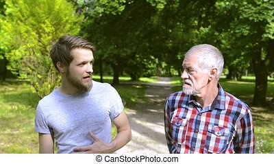 Young man and his senior father on a walk in park. - Young...