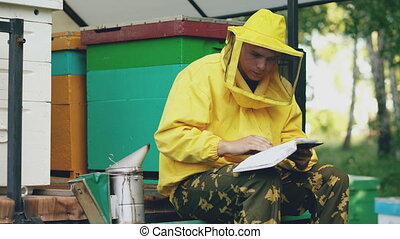 Young beekeeper man write in notepad checking harvest while...