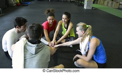 Young people in gym motivating themselves, stacking hands. -...