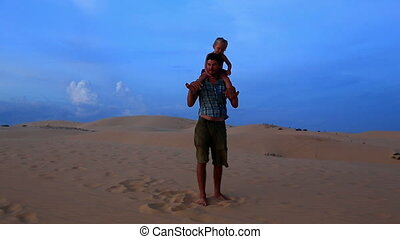 Father Walks with Small Girl on Shoulders against Dunes Blue Sky