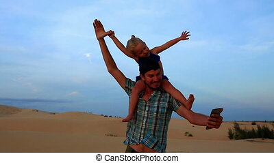 Closeup Father Carries Small Girl Makes Selfie against Dunes...