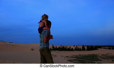 Close Father Walks with Small Girl on Shoulders on Dunes -...