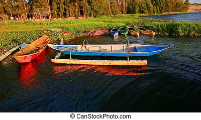 Empty Boats Float at Wooden Pier in Lake by Grass Bank -...
