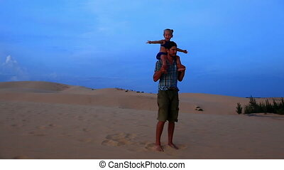 Father Spinning with Small Girl on Shoulders against Dunes...
