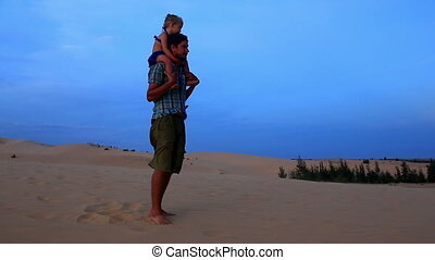 Father Jumps with Small Girl on Shoulders against Dunes Blue...