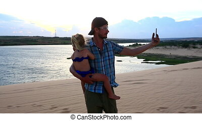 Father Holds Small Girl Makes Selfie on Dune by Lake at...
