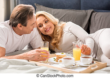 Happy middle aged couple having breakfast together in bed