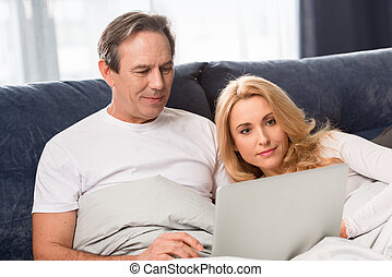 Happy middle aged couple using laptop and lying on bed at...
