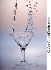 glass with water - Water flows into a glass goblet