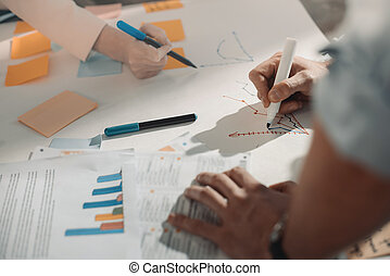 Close-up partial view of young business people working with charts