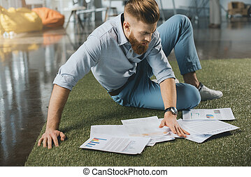 Young bearded businessman sitting on floor and working with...