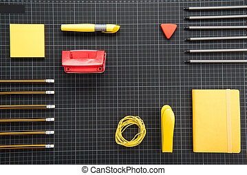 Top view of organized various office supplies on black...