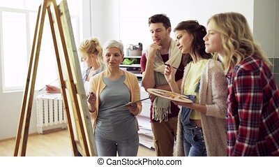 group of artists discussing painting at art school -...