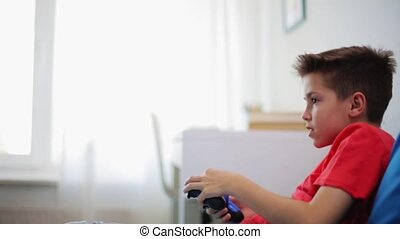happy boy with gamepad playing video game at home -...