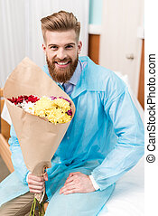 front view of happy young man with flowers in hospital