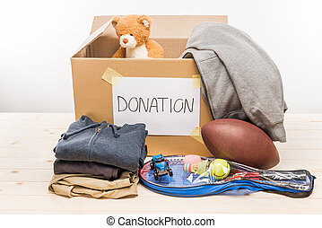 cardboard box with donation clothes and different objects on...