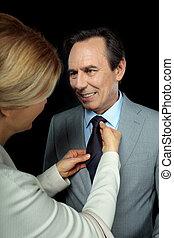 blonde business woman adjusting man's tie on black