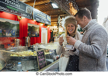 Couple Sharing French Food at Christmas Market - A couple at...