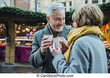 Elderly Couple Drinking Hot Drinks at Christmas Market -...