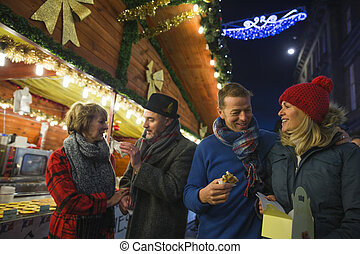 Eating Waffles At The Christmas Market - Mature couples are...