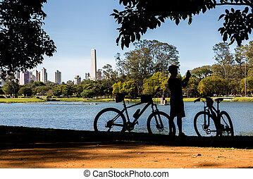 Ibirapuera Park, Sao Paulo, Brazil - Cyclist by the lake in...