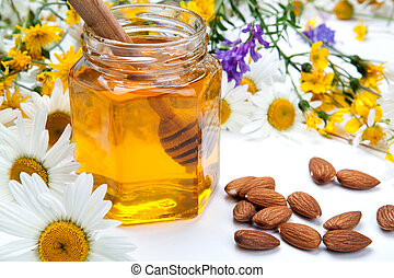 Still life of fresh honey and flowers - fresh honey in a...