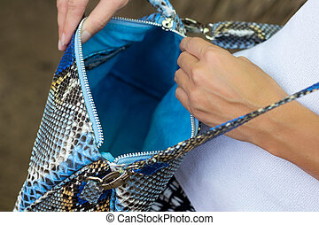 Closeup woman hands with luxury handmade snakeskin handbag, outdoors, fashion look.