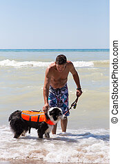 Holding onto dog in a life jacket at the beach