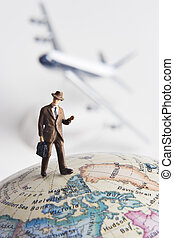 Frequent flier - Business figurine on earth globe with toy...