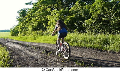 Young girl riding on bike on country road at sunset, slow...