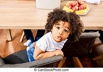 Afro child sitting at the table - Portrait of a young afro...