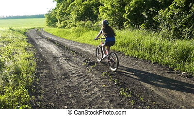 Young girl riding on bike on rural road at sunset, slow...