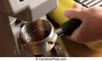 Male hand and coffee grinder. Portafilter with ground...