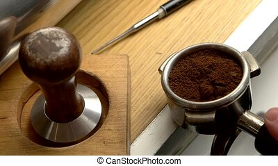 Male hand tamping coffee. Portafilter and tamper.
