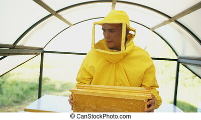 Stedicam shot of beekeeper with wodden frames walking and...
