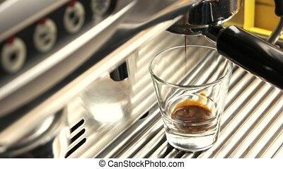 Close up of espresso machine. Dark coffee in shot glass....